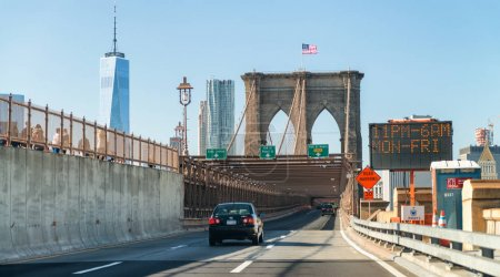 NEW YORK CITY - OCTOBER 20, 2015: Cars speed up on Brooklyn Bridge. Traffic is very high on this road.