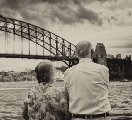 Elderly couple enjoy Sydney Harbour Bridge view at sunset.