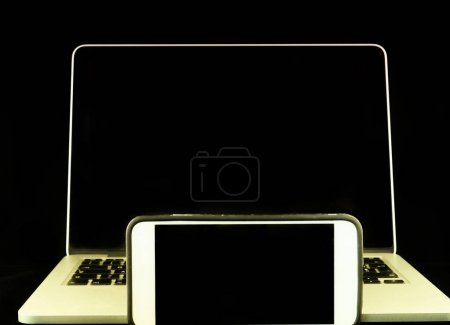 Modern smartphone with laptop computer on background. Isolated on black.