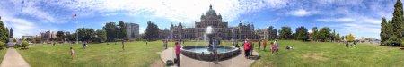 VICTORIA, CANADA - AUGUST 14, 2017: Tourists visit Parliament and city park. Vicotoria is a famous tourist destination in Vancouver Island.