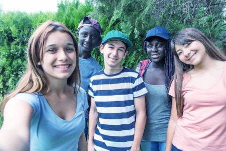 Foto de Grupo de multi étnica adolescentes al aire libre haciendo autorretratos - Imagen libre de derechos