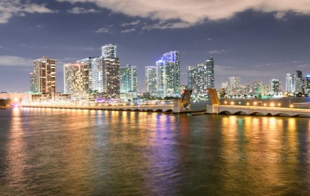 Miami night skyline from MacArthur Causeway. Buildings reflections.