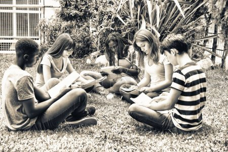 Multi ethnic teenagers friends making school tests outdoor, seated on a park.