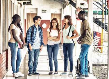 Group of mixed races teenagers talking standing in school hallway.