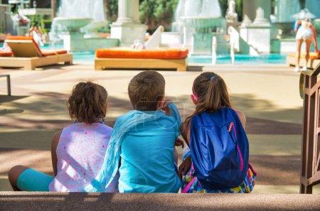 Photo pour Vue arrière de trois jeunes enfants profitant de la vue sur l'espace de détente en plein air en saison estivale. Concept de voyage, vacances et vacances - image libre de droit