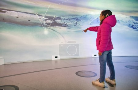 Photo for Young girl visiting interactive museum, pointing finger to the screen. - Royalty Free Image