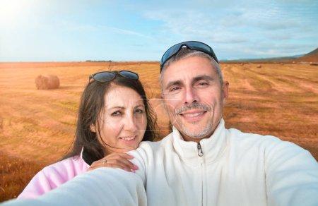 Photo pour Couple heureux prenant un selfie en pleine campagne avec des balles de foin sur le fond. - image libre de droit