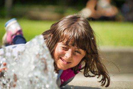 Photo pour Joyeux visage d'une jeune fille jouant avec l'eau dans le parc. - image libre de droit