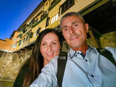 Photo pour Couple prenant selfies sous Ponte Vecchio. Old Bridge, Florence. - image libre de droit