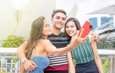 Photo pour Trois amis asiatiques prenant selfies en plein air. Concept d'amitié et de vacances. - image libre de droit