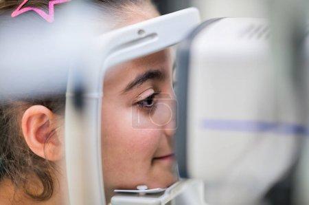 Photo pour Jeune fille visitée par un ophtalmologiste à la clinique. Diagnostic et correction de la vision chez l'enfant. - image libre de droit