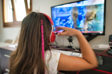 Photo for Young girl wearing headphones looking to big computer screen, back view - Royalty Free Image