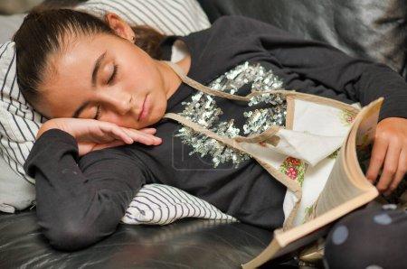 Photo pour Jeune fille dormant sur le canapé lisant un livre. - image libre de droit