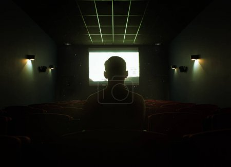 One man sitting in empty cinema hall
