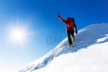 Foto de Deportes extremos de invierno: el escalador alcanza la cima de un pico nevado en los Alpes. Conceptos: determinación, éxito, fuerza . - Imagen libre de derechos