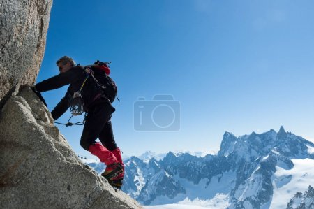 Climbing in Chamonix. Climber on the stone wall of Aiguille du Midi in Mont Blanc, France.
