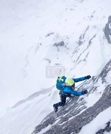 Female climber in the storm during an extreme winter climb.