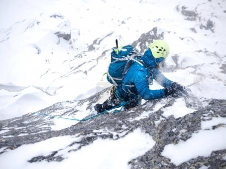 Climber in the storm during an extreme winter climb. West