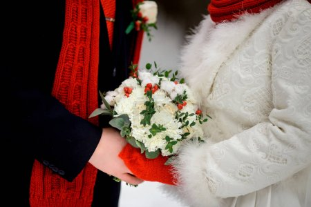 Winter bouquet in the hands of the bride and groom
