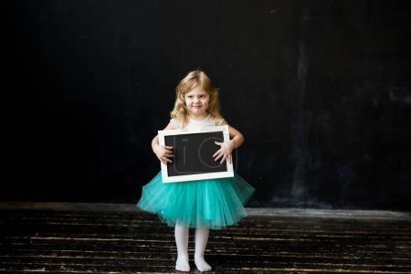 Cute little girl with a frame in her hands