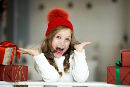 Beautiful little girl celebrates Christmas. New Year's holidays. Happy girl in a Christmas costume with gift