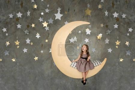 little girl in sitting on big moon. Little girl dreaming