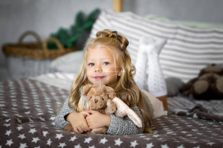 Cute little girl is playing with a toy bear on the bed