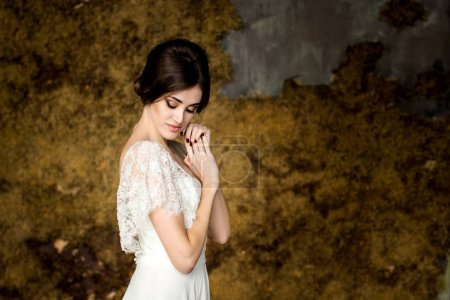 Bride in white dress sitting on chair indoors in dark studio interior like at home.