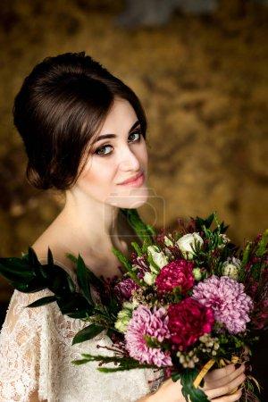 elegant bride with flower bouquet in hands. Portrait of beautiful bride in white dress