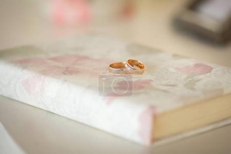 Two wedding rings on a book. Wedding details.