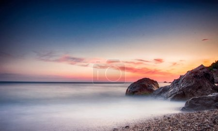 Photo for Calm seascape with rocky coast on twilight - Royalty Free Image