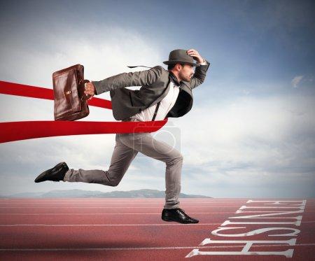 Photo pour Homme d'affaires avec sac au-delà du ruban rouge à l'arrivée d'une course - image libre de droit