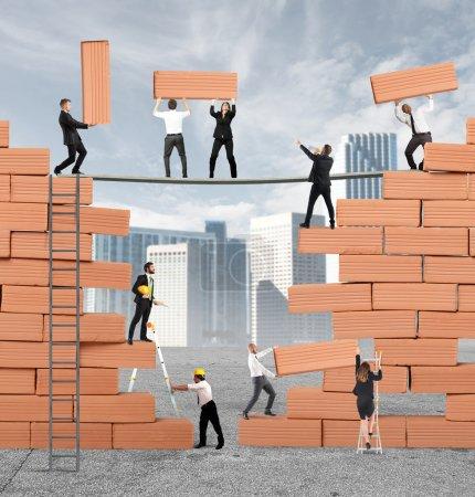 Photo pour Gens d'affaires construit ensemble un grand mur de briques - image libre de droit