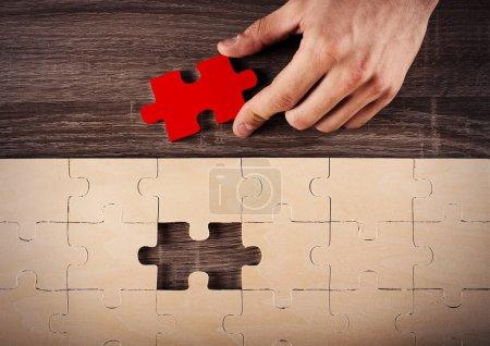 Photo pour Homme d'affaires complétant un puzzle insertion dernière pièce - image libre de droit