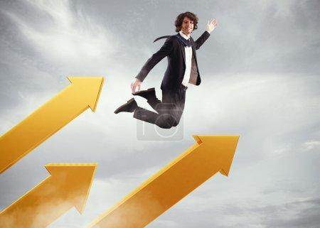 Businessman jumps on big arrows