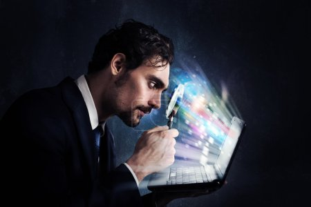 Photo for Businessman looking  with magnifying glass at the computer screen - Royalty Free Image
