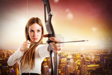 Photo pour Femme d'affaires avec arc et flèche avec vue sur le paysage urbain - image libre de droit