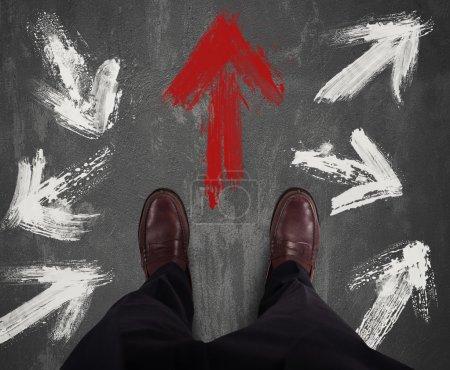 Photo pour Homme d'affaires en décidant de direction et suit la flèche rouge - image libre de droit