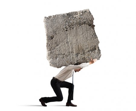Businessman walking with a heavy boulder