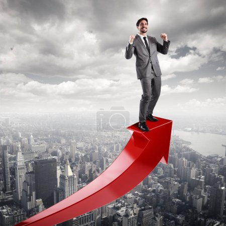 Businessman exults over a red uphill arrow.