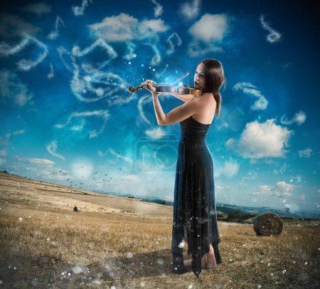 Photo pour Élégante femme jouant du violon sur fond de campagne avec des notes de musique - image libre de droit