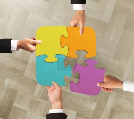 Photo pour Les hommes d'affaires travaillent ensemble pour construire un puzzle coloré - image libre de droit