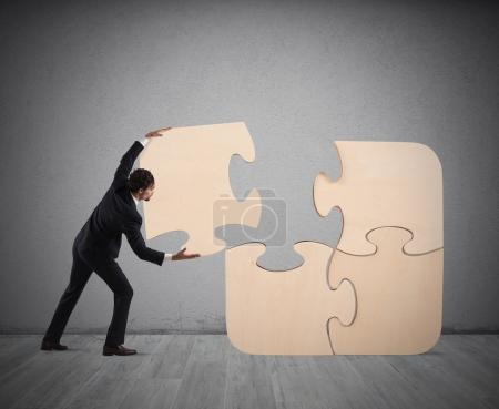 Photo for Businessman complete a big puzzle inserting a missing piece - Royalty Free Image