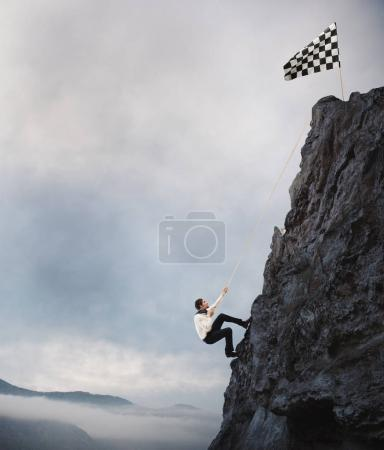 Photo for Businessman climbs a mountain to get to the flag. Achievement business goal and Difficult career concept - Royalty Free Image