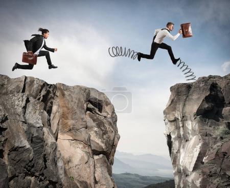 Photo pour Un homme d'affaires avec des ressorts court contre un autre homme d'affaires entre deux montagnes - image libre de droit