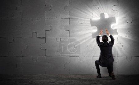 Photo pour Homme d'affaires compléter un puzzle en insérant une pièce manquante - image libre de droit