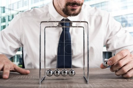 Businessman plays with the pendulum