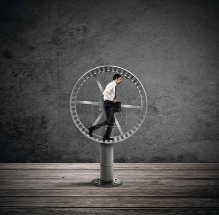 Businessman running on the hamster wheel