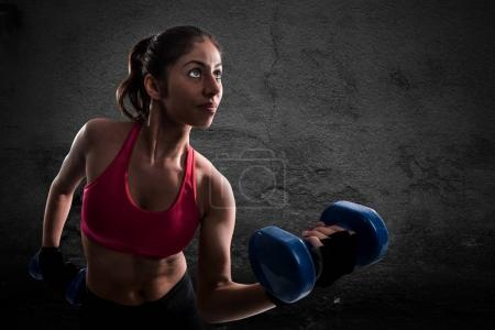Athletic muscular woman training biceps