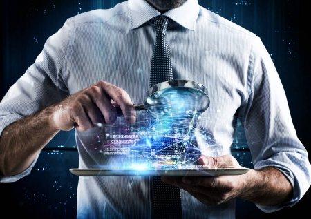 Photo pour Homme regardant avec une loupe sur l'écran d'une tablette - image libre de droit